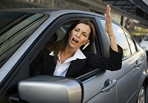 Businesswoman yelling out of car window.